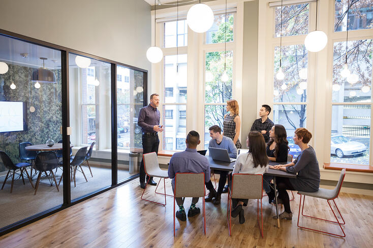 Investors gathering around a conference room table to discuss their new software